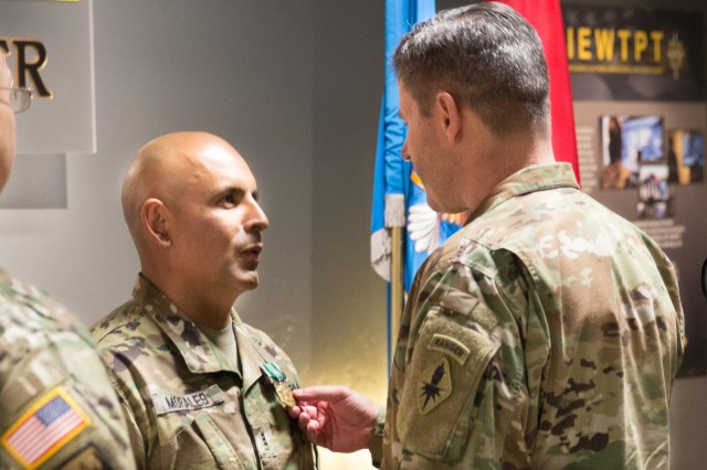 The 2017 USAICoE Distinguished Instructor of the Year, Chief Warrant Officer Byron Morales, receives the Army Commendation Medal from Maj. Gen. Robert Walters, Commander of USAICoE and Fort Huachuca, during a ceremony held at the Military Intelligence Soldier's Heritage Learning Center on Oct. 27.