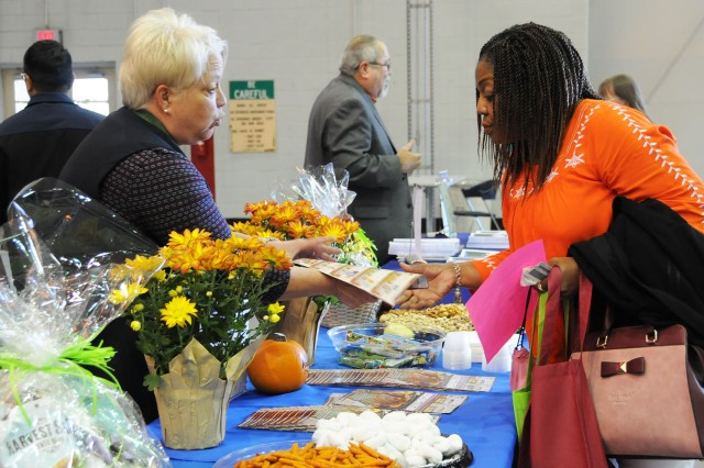 Traci McNair, retired spouse, speaks with Brenda Fitts, Fort Rucker Commissary produce manager, during the 43rd annual retiree health fair at Yano Hall Oct. 27.