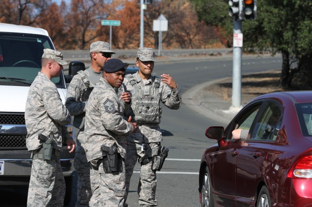 Senior Airman Jess Contreras, right, of the 146th Security Forces Squadron, 146th Airlift Wing (Channel Islands), California Air National Guard, signals a vehicle to move forward at a traffic control point Nov. 2 in Santa Rosa, California, an area hardest hit by October's Northern California wildfires. Air Guardsmen assumed missions that Army Guard units began at the peak of the fires. Assisting in traffic control are 146th Senior Master Sgt. Johnny Gatlin, front, and Capt. Charles B. Rogers, left, of the 129th SFS, 129th Rescue Wing, Moffett Air Guard Base, San Jose. In rear is Contreras' partner, Airman 1st Class Danelle Perey.