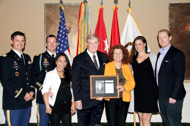 James C. Cooke, U.S. Army Evaluation Center executive director and Senior Executive Service member, stands proudly with his family after his induction into the Operations Research and Systems Analyst Hall of Fame at an induction ceremony hosted by the Army Operations Research Symposium at the Maryland Golf and Country Club in Bel Air Oct. 24. From left to right, Army Capt. Dan Cooke, Army Maj. Mike Cooke and his wife Kristy, James Cooke and his wife Lynnette, and Salina and husband, Matthew Cooke.