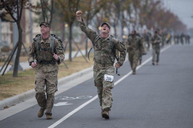 A 2nd Armored Brigade Combat Team, 1st Cavalry Division Soldier raises his hand in triumph as he prepares to finish an 18.6-mile ruck march held in honor of Medal of Honor Recipient, Capt. Emil Kapaun, an Army chaplain, at Camp Humphreys, Republic of Korea, Nov. 2, 2017.