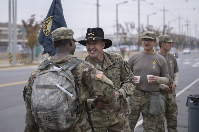 Major Jason Palmer, chaplain, 2nd Armored Brigade Combat Team, 1st Cavalry Division, greets Staff Sgt. Deangello Wiggins (left), S4 Mobility noncommissioned officer in charge, 2ABCT, as he crosses the finish line after an 18.6 mile ruck march in honor of Medal of Honor Recipient Capt. Emil Kapaun, an Army chaplain at Camp Humphreys, Republic of Korea, Nov. 2, 2017.