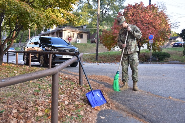Pfc. Kim, Hee-cheol, HHC, USAG Yongsan, sweeps fallen leaves during Fall Cleanup 2017 behind Bldg. 4305.
