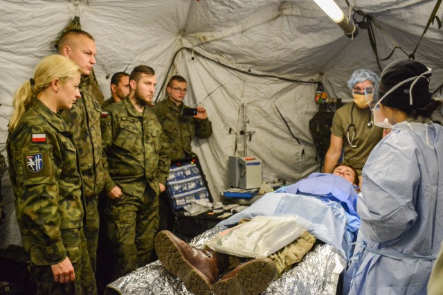 Maj. Phuoc Nguyen, a general surgeon for the 212th Combat Support Hospital, provides a demonstration of field surgical care with Lt. Col. George Johnson, a Certified Registered Nurse Anesthesiologist, Oct. 31, 2017. The Polish 15th Mechanized Brigade observed the training in order to increase interoperability during future medical operations.