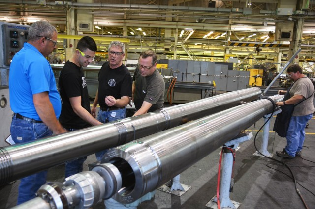 Arsenal Apprentice Program Supervisor Robert Day, left, explaining to students from the Hudson Valley Community College's Advance Manufacturing class an operation that is being performed on a 155mm tube for a Paladin howitzer.  The Arsenal has closely worked with the college for decades in the development of Arsenal machinist apprentices.