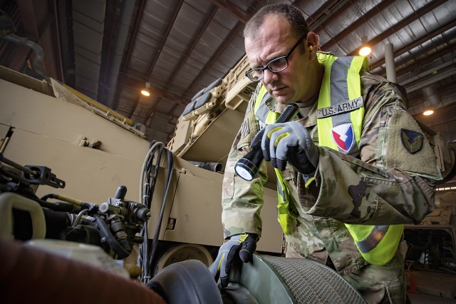 Staff Sgt. Anthony Allen, contract officer representative, Army Field Support Battalion-Kuwait, examines the engine of an M1A2 Abrams Main Battle Tank during a quality assurance inspection at Camp Arifjan, Kuwait, Oct. 31. (U.S. Army Photo by Justin Graff, 401st AFSB Public Affairs)