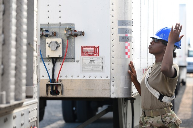 U.S. Army Specialist Adrianne Reese, cargo specialist from the 119th Inland Cargo Transfer Company, 11th Transportation Battalion, 7th Transportation Brigade (Expeditionary) based at Joint Base Langley-Eustis, Va., guides a 53-foot trailer into place on the shipyard of the Port of Ponce, Puerto Rico, Nov. 4, 2017. The trailers included generators, temporary living and laundry facilities, as well as other humanitarian relief effort supplies for the island of Puerto Rico. (U.S. Air Force photo by Staff Sgt. Teresa J. Cleveland)