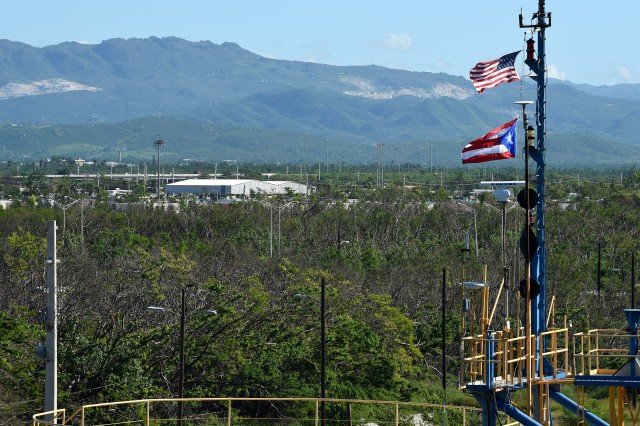 A U.S. flag and Puerto Rico flag fly high above the Port of Ponce, Puerto Rico, Nov. 3, 2017. Ponce has both sea and air ports, making it an ideal location for humanitarian relief efforts after hurricane Maria. (U.S. Air Force photo by Staff Sgt. Teresa J. Cleveland)