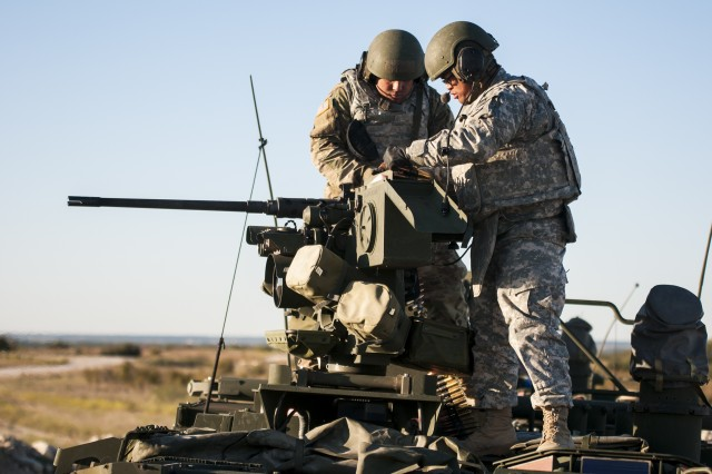 Two Soldiers assigned to the Army Reserve's 300th Chemical Company out of Morgantown, W. Va., load a belt of ammunition into a .50-caliber Browning machine gun on a Stryker M1135 Nuclear, Biological and Chemical Reconnaissance Vehicle during a gunnery at Fort Hood, Texas, Oct. 28, 2017. The gunnery gave the troops the opportunity to get required training on their weapons systems.