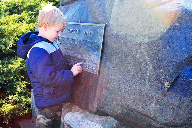 A first-grade student from the Rock Island Center for Math and Science checks out a plaque attached to a boulder at Memorial Field Nov. 8. (Photo by Jon Micheal Connor, ASC Public Affairs)