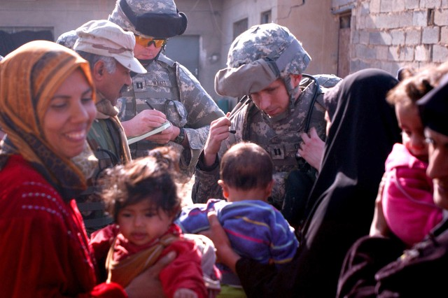 A Soldier of C Company, 210th Brigade Support Battalion, discusses an Iraqi boy's illness with 2nd Battalion, 4th Brigade, 6th Iraqi Army Division medic Sgt. Maj. Hassan at a medical operation Dec. 25, 2006, in the Al-Jazir neighborhood of Mahmudiyah, Iraq.
