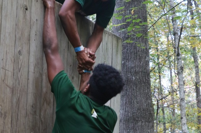 """A Cadet from Grayson High School, Logansville, Georgia, uses all of his strength to get his teammate over the 11-foot wall on the obstacle course known as """"the Gauntlet"""" during the JROTC's National Raider Championships held at the Gerald Lawhorn Boy Scout Camp in Molena, Georgia, Nov. 4-5."""