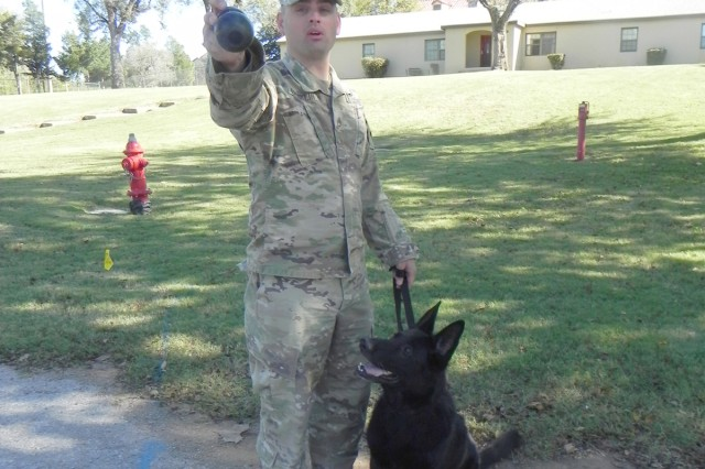 Staff Sgt. Daniel Franklin, plans NCO, 902nd Military Working Dog Detachment at Fort Sill, Okla., stands with Sue, a patrol/explosive detector dog, he adopted this year.