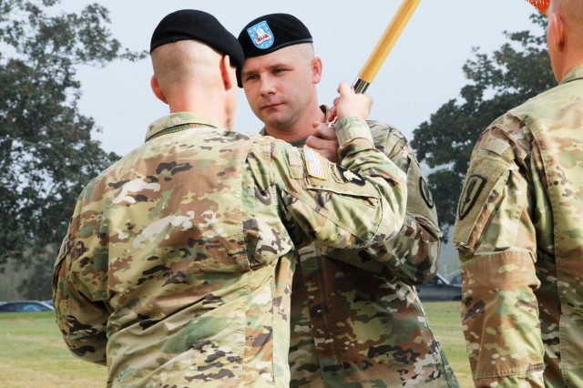 Command Sgt. Maj. Devon M. Weber, 1-13th Avn. Regt. command sergeant major, assumes responsibility from Command Sgt. Maj. George S. Webster as he accepts the unit colors from Lt. Col. Kevin E. McHugh, 1-13th Avn. Regt. commander, during a change of responsibility ceremony on Howze Field Tuesday.