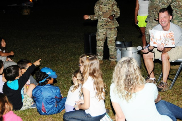 Col. Brian E. Walsh, Fort Rucker garrison commander, tells the story of 'Stone Soup' with the help of Spc. Mykea Carrol, 1-145th Avn. Regt.; Sgt. Sam Arredondo, 1-13th Avn. Regt.; and Spc. Joshua Moore, 1-212th Avn. Regt., during Camping Under the Stars on West Beach at Lake Tholocco Friday.