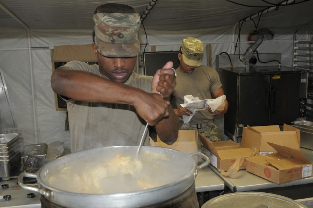 (left) Pfc. Willie Mills, a food service specialist with headquarters support company, headquarters and headquarters battalion, 25th Infantry Division, and Leron Howard a food service specialist with headquarters support company, headquarters and headquarters battalion, I Corps work in a Mobile Kitchen Trailer (MKT) during a Warfighter exercise (WFX) 18-2 at Camp Hovey, South Korea, on Nov. 8, 2017. MKT's are crucial during WFX 18-2, allowing soldiers to prepare meals in a field environment.
