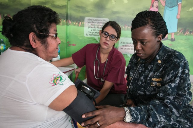 AHUACHAPAN, El Salvador (Sep. 8, 2016) - U.S. Navy Lt. Cmdr. Ebony Ferguson, a clinical nurse specialist assigned to Fort Belvoir, assists Dr. Gabriela Menjivar M.D., a health worker with Operation Blessing's Medical Brigade, check a patient's vitals at a temporary treatment site in Ahuachapán, El Salvador during Southern Partnership Station 2016 (SPS-16).  Operation Blessing's Medical Brigade is a non-for-profit mobile patient care unit established to provide medical service to those affected by natural disaster and render aid to rural areas. SPS-16 is an annual series of U.S. Navy deployments focused on subject matter expert exchanges with partner nation militaries and security forces in Central and South America and the Caribbean. U.S. military teams work with partner nation forces during naval-focused training exercises, military-to-military engagements and community relations projects in an effort to enhance partnerships with regional maritime activities and improve the operational readiness of participants. (U.S. Army photo by Private First Class Liem Huynh/Released)
