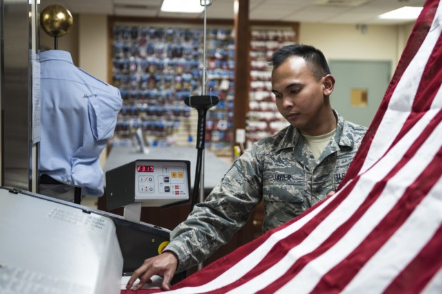 Inside the Charles C. Carson Center, located at Dover Air Force Base in Dover, Del., Senior Airman John Paul Javier presses the United States National Flag for use during mortuary affairs operations, Oct. 24, 2017. The Charles C. Carson Center is home to the Port Mortuary, which is responsible for returning all Department of Defense service members, civilians, and contractors who perish during contingency operations overseas. The 73,000 square foot facility was built in 2003 at a cost of $30 million.