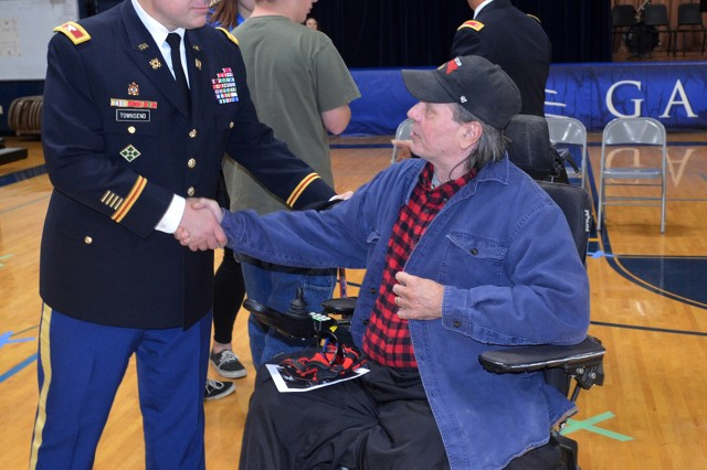 Col. Stacy Townsend, director, Distribution Management Center, ASC, greets a veteran during an assembly at Galva High School in Galva, Illinois, Nov. 10.