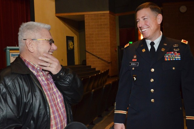 Col. Michael B. McNeely, ASC's director of Army Prepositioned Stocks, shares a laugh with a veteran following the Goose Lake, Iowa, Veterans Day assembly at the Northeast Community School District Auditorium, Nov. 10. McNeely was the keynote speaker at the event that drew more than 450 students and community members
