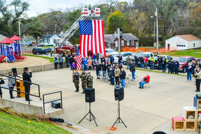 A crowd assembles at Hero Street Memorial Park before the backdrop of a large American flag hung from the ladder of a fire truck to commemorate Veterans Day at Silvis, Illinois, Nov. 11.