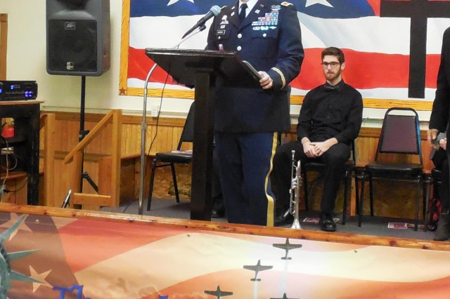 Col. Grant Morris, ASC, speaks at a Veterans Day observance hosted by American Legion Post 227 in East Moline, Illinois, as Kyle Jecks, who performed trumpet solos at the observance, looks on.