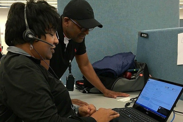 USASAC's Carol Morales, left, and FEMA's Cornelius Jackson discuss disaster assistance at the FEMA call center in Carson City. Jackson serves as Morales' mentor at the call center, where she spends 12-hour days assisting hurricane survivors.