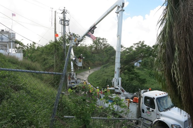 Soldiers in buckets winch lines between adjacent poles along the side of the road in Las Colas, Puerto Rico. Capt. Tom Hickey, commander of the unit, estimates the unit has run about 15 kilometers of power line in the hillside community 47.5 kilometers east of San Juan.
