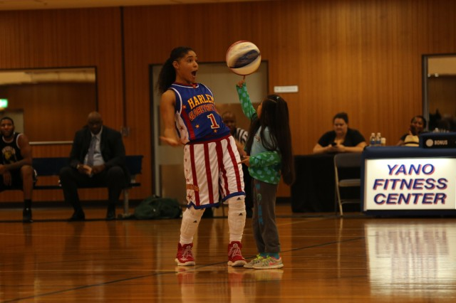 """Ace"" Jackson, a member of TOHG, shows a spectator how to spin a basketball on her finger during TOHG's performance for the Camp Zama community Nov. 9, 2017 at Yano Fitness Center. (U.S. Army photo by Noriko Kudo)"