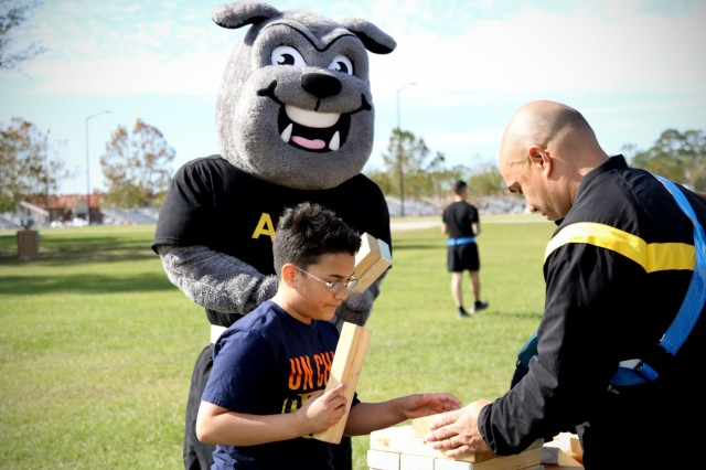 Rocky, the 3rd Infantry Division mascot, enjoys a game of Jenga with a family during a Family Fun Day at Newman Field at Fort Stewart, Georgia, Nov. 14, 2017. The Family Fun Day was one of many events during Marne Week, a celebration for Soldiers to compete in team sports and recreational group activities while honoring the division's service to the nation. This month marks the centennial anniversary of the Marne Division. Born out of World War I, the division has answered the nation's call for 100 years.(U.S. Army photo by Staff Sgt. Sierra A. Melendez, 50th Public Affairs Detachment, 3rd Infantry Division, Public Affairs)