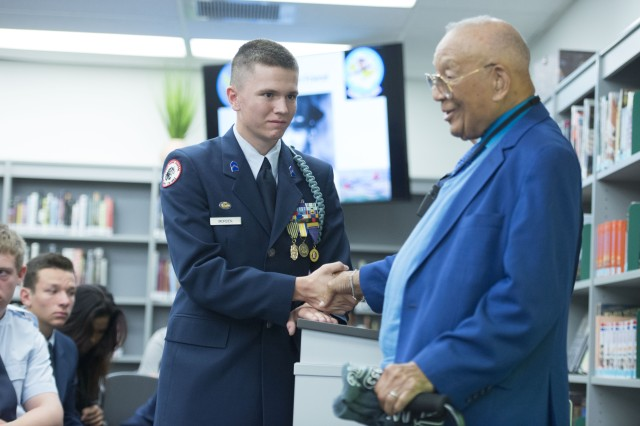 Chris Morden, a JROTC student at Vista High School (Calif.) presents his school's JROTC patch and t-shirt to retired Lt. Col. Robert Friend. Friend, one of the last surviving Tuskegree Airmen, spoke to students at Vista and Fallbrook Union High Schools in southern California, Nov. 2.