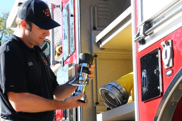 Jordy Fault, Fort Rucker civilian fire fighter, inspects the hose equipment on a fire truck Nov. 11.