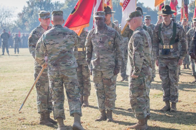 From left, Maj. Gen. Wilson A. Shoffner, incoming FCoE and Fort Sill commanding general, receives the unit colors from Lt. Gen. Michael Lundy, reviewing officer. Also participating in the symbolic exchange were FCoE and Fort Sill Command Sgt. Maj. Carl Fagan, and outgoing Commanding General Maj. Gen. Brian McKiernan, Nov. 9, 2017, at Old Post Quadrangle.