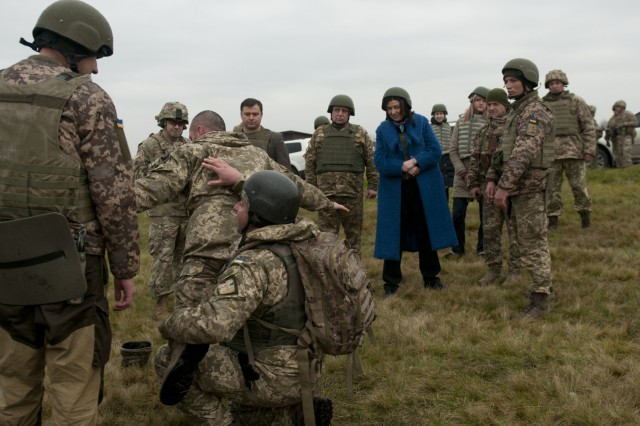 Oksana Syroyid, Vice Speaker of the Ukrainian parliament, known as the Verkhovna Rada of Ukraine, and fellow parliament member Taras Pastukh watch as Ukrainian soldiers demonstrate how to search a detainee at the Yavoriv Combat Training Center on the International Peacekeeping and Security Center in Western Ukraine on Nov. 13. (Photo by Capt. Kayla Christopher, 45th Infantry Brigade Combat Team)