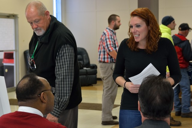 Arsenal Morale, Welfare, and Recreation Specialist Sheryl Melican, right, and Arsenal Manufacturing Support Division Chief Tim Allard, standing left, getting critical information regarding future health benefits.