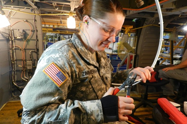 Spc. Ashtyn Zimmerman trims wire from a D-Ice Box to prevent frost on UH-60 rotor blades at Corpus Christi Army Depot where she can practice avionics, Nov. 9, 2017. She and the other Utah National Guard members from D Company, 2-211th General Support Aviation Battalion, are preparing for an upcoming deployment this month with the kind of helicopter maintenance practice that only the Corpus Christi Army Depot could provide.