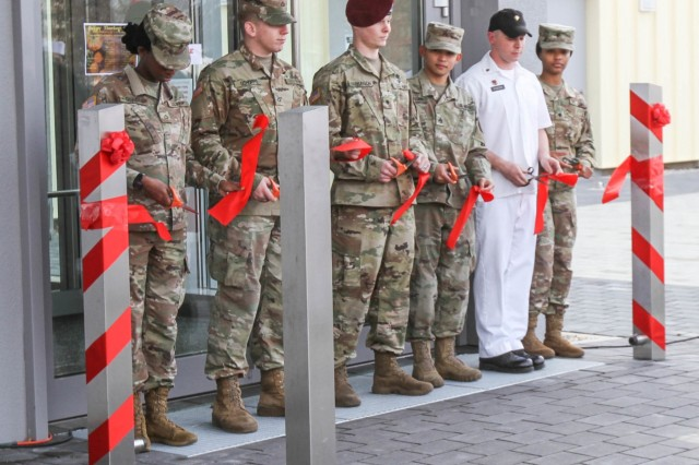 RHINE ORDNANCE BARRACKS, Germany - (Left to right) Private First Class Renee Quashie, automated logistical specialist assigned to 10th Army Air and Missile Defense, Private First Class Andrew Schoppe, chemical, biological, radiological and nuclear specialist assigned to 92nd Military Police Company, Spc. Joshua Parkinson, parachute rigger assigned to 5th Quartermaster Theater Aerial Delivery Company, Sgt. Mark Lacbain, nutrition care NCOIC assigned to 212th Combat Support Hospital, Spc. Robert Foster, culinary service specialist assigned to 10th AAMDC and Spc. Amber Green, a human resource specialist assigned to Headquarters and Headquarters Company, USAG Rheinland-Pfalz cut the ribbon in front of the new Defender Café at a ceremony Nov. 20. (Photo by Robert Durr, 10th AAMDC PAO)