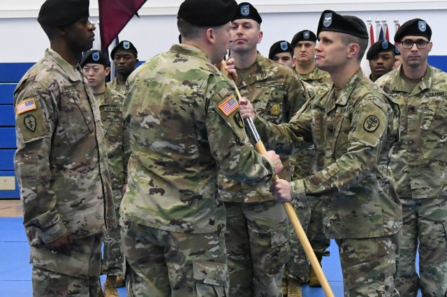 STUTTGART, Germany -- Col. Theodore Brown, outgoing commander, Stuttgart Army Health Clinic, passes the unit's guidon to Col. Mark D. Swofford during a change of command ceremony November 21, 2017 at the Patch Barracks Gym. During the ceremony Brown relinquished command to Lt. Col. Keith Burnette. In remarks by Swofford, Brown was recognized as being a dependable leader who was active in the community in promoting health and wellness and also as a man of character. Photo by Ms. Shaylee Borcsani, U.S. Army Medical Department Activity Bavaria Public Affairs (Released)