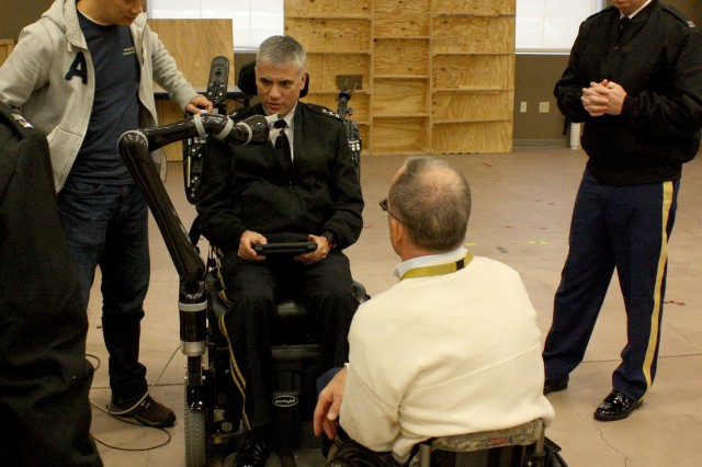 Lt. Gen. Paul M. Nakasone, commanding general, U.S. Army Cyber Command, received a demonstration Nov. 16 of the Jacontrol robotic arm control application at the Human Engineering Research Laboratories, University of Pittsburgh, a part of the U.S. Department of Veterans Affairs Center for Wheelchairs and Associated Rehabilitation Engineering. With him are Drs. Joshua Chung and Rory Cooper.