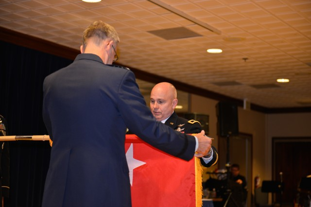 U.S. Air Force Gen. John Hyten, commander of U.S. Strategic Command, left, and U.S. Army Col. Thomas James, deputy commander of Joint Functional Component Command for Space, unfurl the general officer flag during a ceremony in which James was promoted to the rank of brigadier general at Peterson Air Force Base, Colorado, Nov. 14. As a component of U.S. Strategic Command, JFCC Space is responsible for executing continuous, integrated space operations to deliver theater and global effects in support of national and combatant commander objectives. JFCC Space coordinates space operational-level planning, integration and coordination to ensure unity of effort in support of military and national security operations, and support to civil authorities.