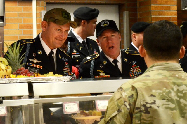 U.S. Army Command Sgt. Maj. Jay Morse (CTR) serves a Soldier his Thanksgiving meal at the Warrior Sports Cafe Dining Facility at 7th Army Training Command's Joint Multinational Readiness Center, Hohenfels, Germany, Nov. 22, 2017. (U.S. Army photo by Staff Sgt. David Overson)
