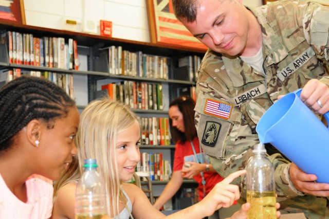 CW4 Blake Leibach, C Co., 1-212th Avn. Regt., lends a hand to Aniya Tuner and Alyssa Hansen, military family members, during a previous Mad Scientist Workshop at the Center Library in August.