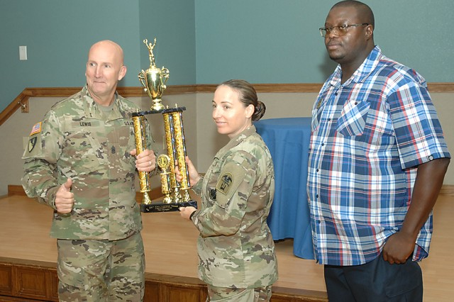 From left, Command Sgt. Maj. William Lewis, 554th Engr. Bn. command sergeant major, and Lt. Col. Christina Cook, 554th Engr. Bn. commander, hold up the Commander's Cup Championship Trophy after receiving it from FMWR Chief of Sports Coleman Swinton during an awards ceremony Nov. 14. It is the third consecutive year the 554th Engr. Bn. has won the points race, this year earning 1,678 points.