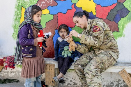 Chief Warrant Officer 3 Kaylan Harrington, Afghan National Army Special Operations Advisory Group mentor, assists with the Afghan Commandos' routine essential items distribution at the Camp Commando medical clinic, Kabul, Nov. 6, 2017. All items provided to the Afghan woman and children are donated from local villages.