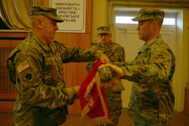 YAVORIV, UKRAINE -  Col. Dave Jordan, the 45th Infantry Brigade Combat Team commander, and Command Sgt. Maj. Christopher Miller, the 45th IBCT senior enlisted soldier, cases the 45th IBCT's colors during a Joint Multinational Training Group - Ukraine (JMTG-U) ceremony here Nov. 22. During the ceremony Soldiers from the New York Army National Guard's 27th Infantry Brigade Combat Team (IBCT) took command of the JMTG-U from the Oklahoma National Guard's 45th IBCT, who have been in Ukraine since January.