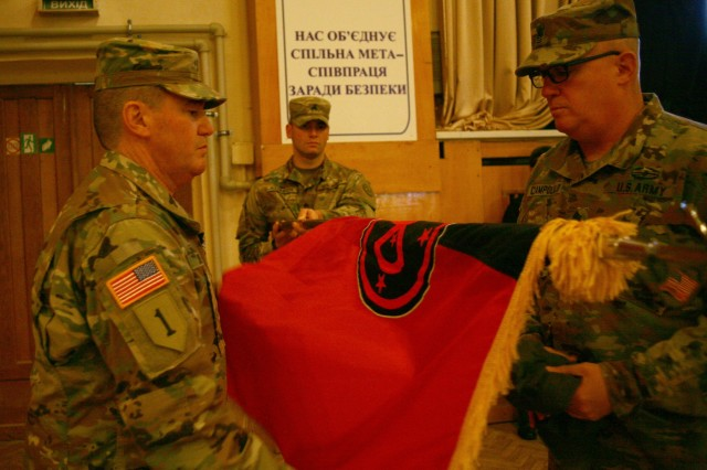 YAVORIV, UKRAINE -  Col. Dennis Deeley, the Joint Multinational Training Group - Ukraine commander, and Command Sgt. Maj. Thomas Ciampolillo uncases the 27th Infantry Brigade Combat Team's colors during a JMTG-U Transfer of Authority ceremony here Nov. 22. During the ceremony Soldiers from the New York Army National Guard's 27th Infantry Brigade Combat Team (IBCT) took command of the JMTG-U from the Oklahoma National Guard's 45th IBCT, who have been in Ukraine since January.