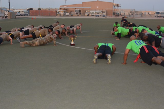 "171122-A-DQ480-002 CAMP ARIFJAN, Kuwait- Players from the Area Support Group-Kuwait Turkey Bowl teams conduct pushups after the game, Camp Arifjan, Kuwait, Nov. 22, 2017. Only the losing tam was required to conduct the pushups, but the victorious enlisted team conducted the exercise as well in honor of the ""One Team, One Fight"" spirit of the unit. (U.S. Army photo by 1st Lt. Vanessa Rios)"