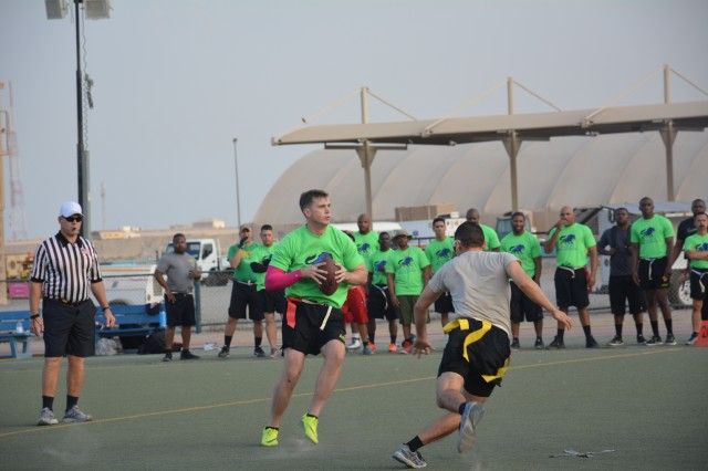 171122-A-DQ480-003 CAMP ARIFJAN, Kuwait- Staff Sgt. William Mitchell, quarterback and Enlisted Team Captain, prepares to pass to his teammate during the Area Support Group-Kuwait Turkey Bowl, Camp Arifjan, Kuwait, Nov. 22, 2017. (U.S. Army photo by 1st Lt. Vanessa Rios)