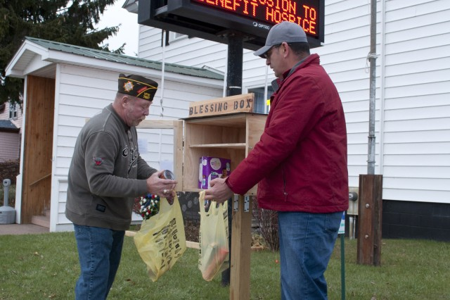 Roman Espinoza helps VFW vice commander Joe Martel place donations inside a newly installed Blessing Box at the Dionne Rumble Veterans of Foreign Wars Post 7227 in Carthage on Nov. 15.