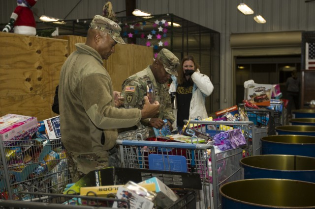 Col. Flint Patterson, commander of the 4th Cavalry Multi-Functional Training Brigade, left, and Command Sgt. Maj. Christopher Crawford, command sergeant major of 4th Cav MFTB, donate gifts to the Red Cross Santa's Workshop program Nov. 22, 2017, at the Red Cross warehouse on Fort Knox, Ky. The donated gifts are used by the Red Cross to provide parents an opportunity to shop for Christmas at no cost.